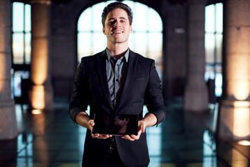 Homme souriant montrant une tablette tactile