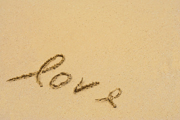 Conceptual handwritten love text in sand