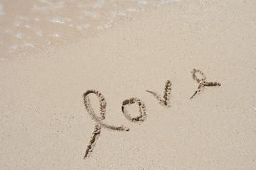 Conceptual handwritten love text in sand