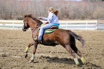 Young blonde woman barrel racing