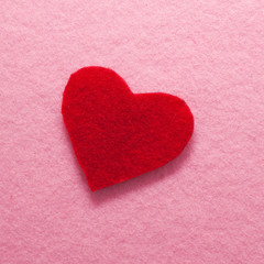 Felt red heart on pink background.