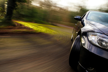 Side view of black car in turn with heavy blur motion