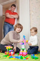 parents and child plays with meccano