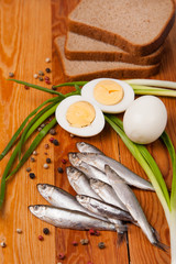 salted anchovies, egg, bread and spring onion on wood