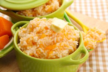 Taste rice porridge with pumpkin in saucepans