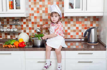 Girl in a cook cap  sits on a kitchen table