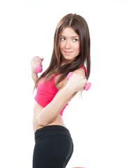Sport woman on diet standing sideways, holding pink dumbbells