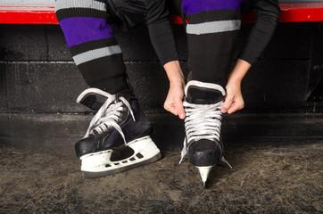 Child Tying Hockey Skates in Dressing Room