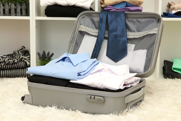 Open grey suitcase with clothing in room