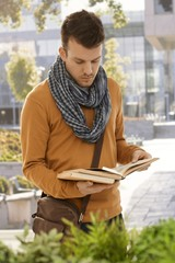 Portrait of male student with books outdoors