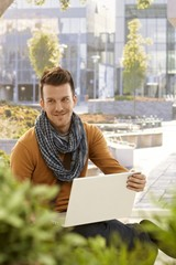 Happy young man with laptop outdoors