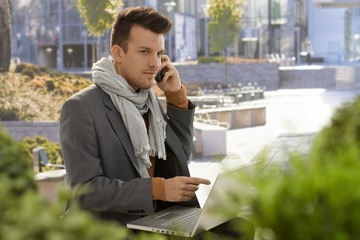 Young businessman talking on mobile outdoors