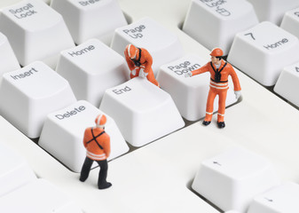 tiny figures of construction engineers removing end key