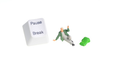 Tiny figure of hiker siting next to pause - break key