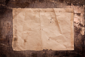 Crumpled empty paper sheet on a dark wooden background