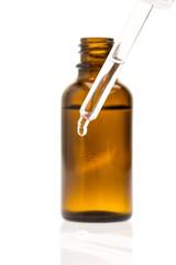 Pipette mit Tropfen vor einer Flasche
