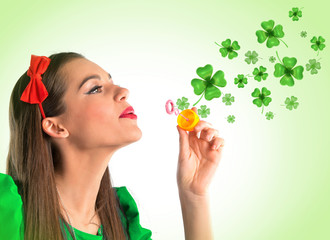 Beautiful woman making four leaf clover bubbles