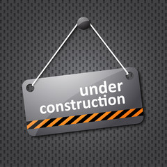under construction sign hung on a textured background