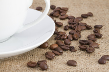 Coffee beans on hessian sack with white cup and saucer