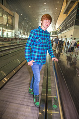 young boy on a moving staircase inside the airport
