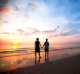 Young couple holding hands on the sea beach at sunset.