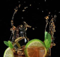 Poster Eclaboussures d eau Cuba libre cocktail on black background