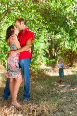 family on vacation with son together in green forest