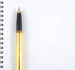 Spiral notebook and golden fountain pen closeup