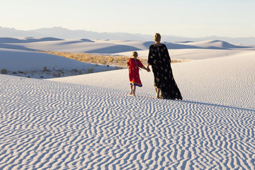 Caucasian mother and daughter walking in desert