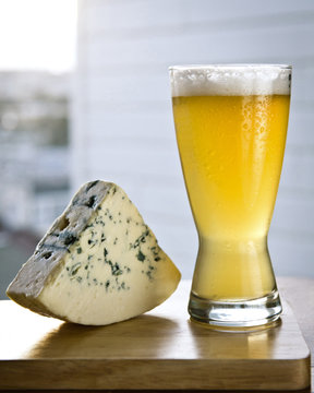Glass of beer with wedge of cheese