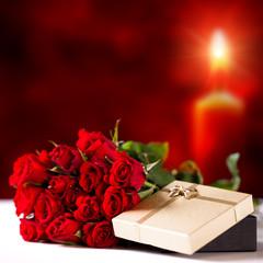 Rosen und Geschenkbox vor Kerzenschein