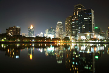 Bangkok urban scene at night with skyline reflection