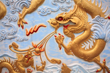 Gold dragon craft and painting on Thai temple wall