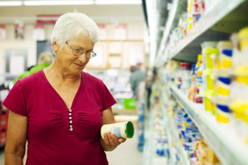 Senior woman checking label on jar