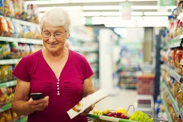 Senior woman texting on mobile phone at supermarket