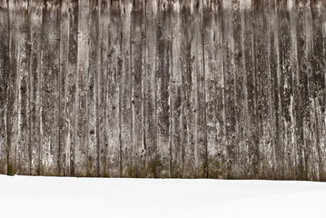 plank wooden wall in winter, snow on the ground