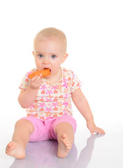 Sweet little baby eating a carrot sitting on the floor on white