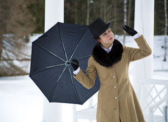 Woman with umbrella feeling winter wind flow