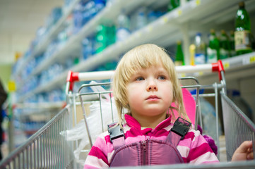 Adorable girl sit in shopping cart in supermarket with bottles o