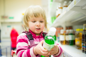 Adorable girl select bottle of soda drink stay in shopping cart