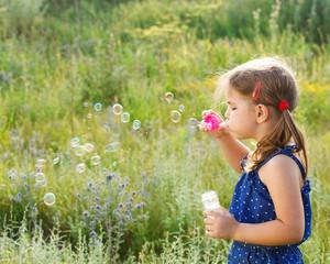 Little cute girl blowing soap bubbles
