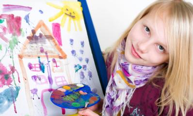 mädchen malt mit Pinsel und Tusche an einer Staffelei