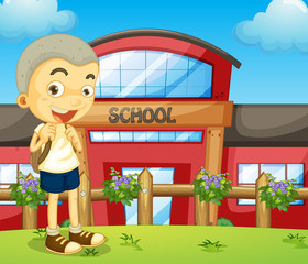 A boy standing near the school