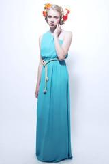Fashion studio shot of young teenage model in long green dress w