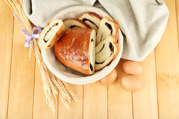 Loaf with poppy seeds in wicker basket, on wooden background