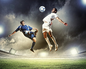 Photo sur Toile Le football two football players striking the ball