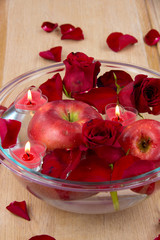 Apple with rose petals in glass bowl