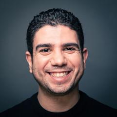 Happy man close up portrait against dark background.