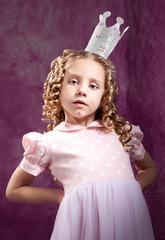 Arrogant little princess posing over dark pink background