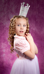 Little princess posing over dark pink background